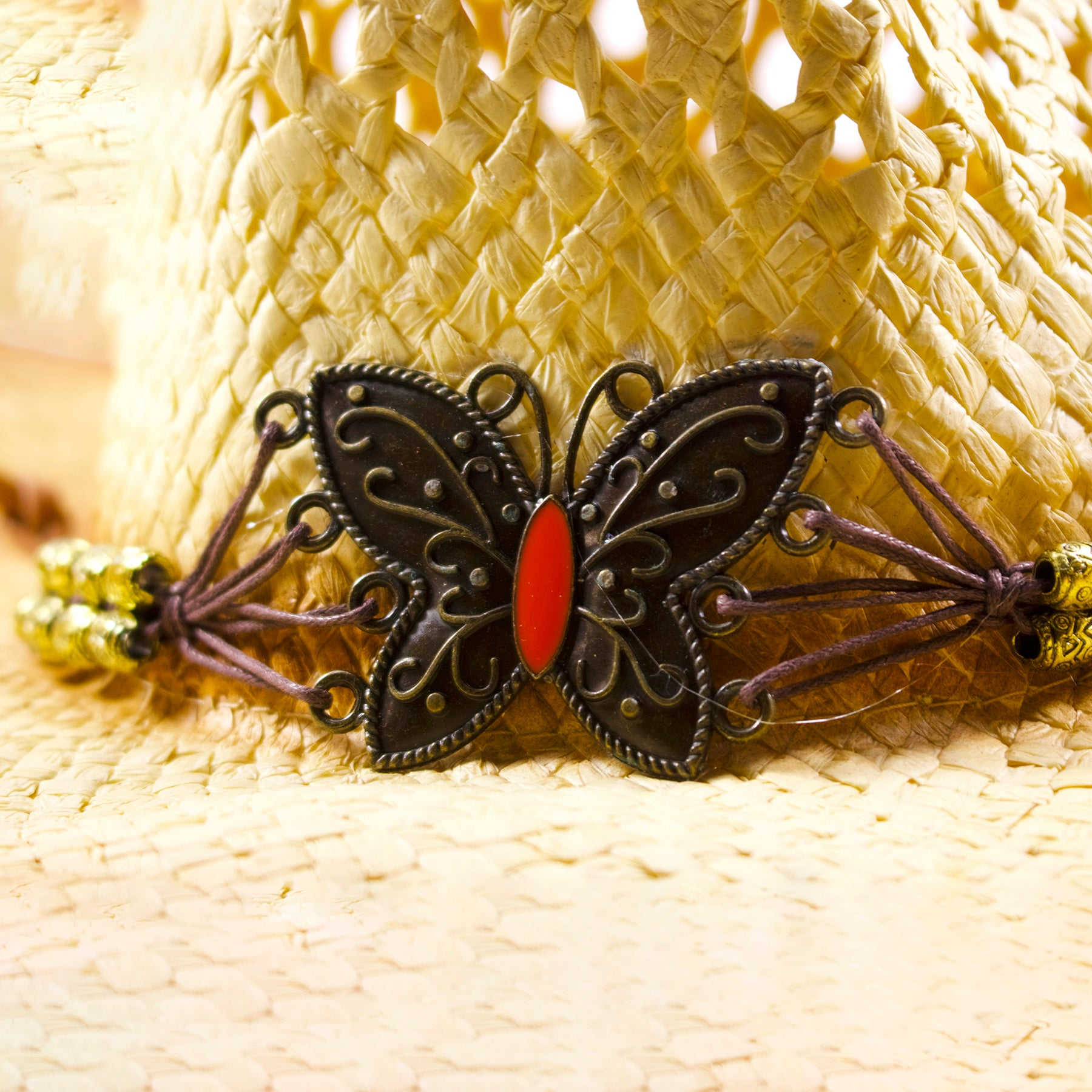 bf82b03567a On the front of the butterfly emblem straw cowboy hat is a metallic  butterfly emblem attached  the metallic butterfly emblem has metallic and  orange ...