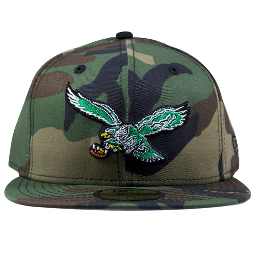 on the front of the philadelphia eagles throwback woodland camouflage fitted cap is the philadelphia eagles throwback logo embroidered in kelly green, white, black, yellow and brown