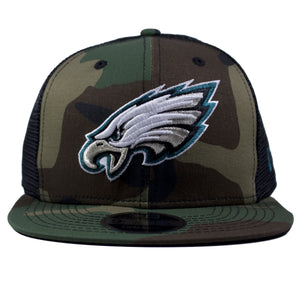 on the front of the camouflage eagles mesh trucker snapback hat is the philadelphia eagles logo embroidered in white, silver, and midnight green