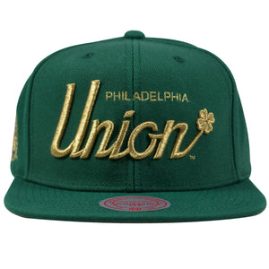 on the front of the Philadelphia union four leaf clover green and gold snapback hat is the Philadelphia Union lettering and a four leaf clover embroidered in metallic gold