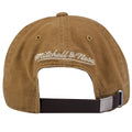 on the back of the cleveland cavaliers tan workman's utility dad hat is the mitchell and ness logo embroidered above a brown leather adjustable strap with metallic buckle
