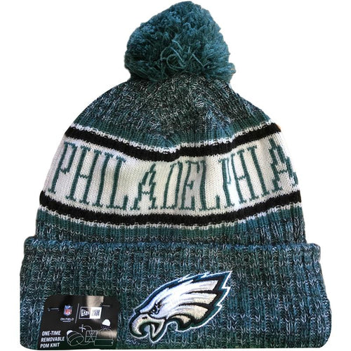 Embroidered on the front of the Philadelphia Eagles 2018 On Field Sideline Winter Pom Beanie is the Eagles logo embroidered in white, silver, black  and midnight green