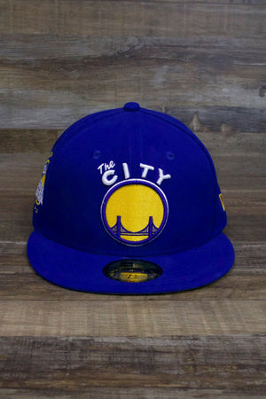 the front of the Golden State Warriors Classic Royal Blue Snapback Hat has a big logo that says the CITY