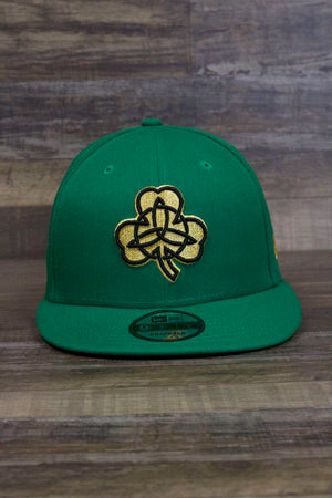 the Boston Celtics 2019 NBA City Series Metallic Gold Clover Irish Green 9Fifty Snapback Hat has a large golden shamrock on the front