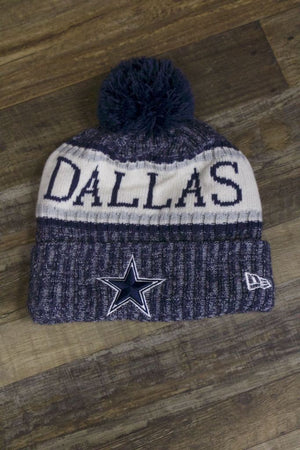 the Dallas Cowboys Winter Pom Beanie | 2018 On-Field Sideline Knit Cowboys Beanie has a dallas wordmark on the front and a big texas star logo