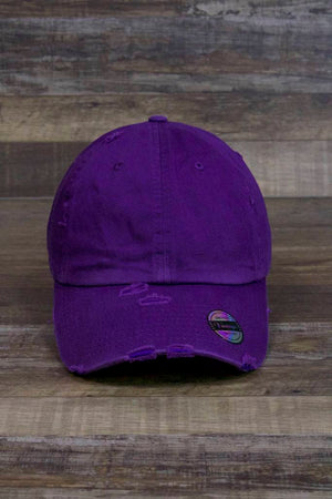 the Plain Purple Distressed Dad Hat | Logo-Free Unmarked Vintage Distressed Purple Baseball Cap for Embroidery has several rips and tears on the front