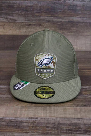 the Philadelphia Eagles Salute to Service 2019 Fitted Cap | Olive Green Philly Birds Military Inspired 59Fifty Fitted Hat has a military patch with stars and bars and the eagle logo on it