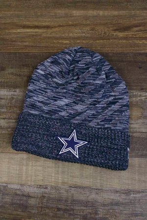 the Dallas Cowboys 2018 On Field Sideline Beanie | Navy Blue Fleece Cowboys Beanie with Diagonal Stripes has a heather knit cuff with a blue Cowboys star on the front