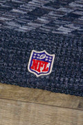 the Dallas Cowboys 2018 On Field Sideline Beanie | Navy Blue Fleece Cowboys Beanie with Diagonal Stripes has an NFL shield embroidered on it