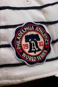 the 1910 World Series Philadelphia Athletics Vintage MLB Fitted Cap | White and Black Stripe Retro Philly Baseball Fitted Cap patch is made of raised embroidery with the Liberty Bell on the patch