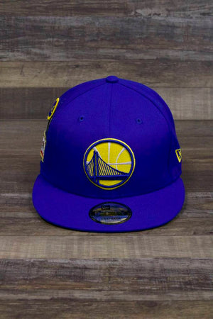 the front of the Golden State Warriors 2018 NBA Draft Snapback Hat | Royal Blue On Court Warriors 9Fifty Snap Back Hat has a round Golden Gate Bridge patch