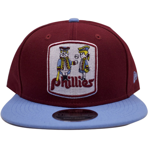 on the front of the throwback philadelphia phillies cooperstown fitted hat is the 1970s phillies logo embroidered on a maroon crown with light blue brim