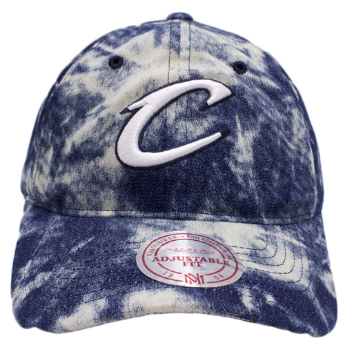 on the front of the cleveland cavaliers acid wash denim dad hat, the cleveland cavaliers logo is embroidered in white and navy blue