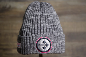 Steelers 2019 Crucial Catch Beanie | Pittsburgh Steelers Grey Winter Hat the front of this steelers beanie is heather grey with the steelers logo in grey with a pink outline