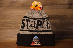 Grey Beanie | Staple X Spike Lee Most Valuable Pigeon Beanie on the front of the spike lee beanie is a grey top with the word staple across the front in black, there are black spots all over the top, with a multi color beanie
