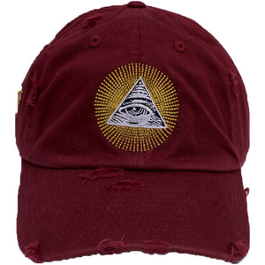 the maroon distressed all seeing eye dad hat has a gold , white and black all seeing eye pyramid logo embroidered on the front of a maroon distressed dad hat