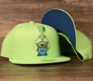 The toy story alien kid's snapback hat features a neon green crown and brim, with a blue under brim