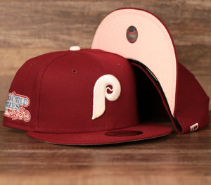 The Philadelphia Phillies Cooperstown Maroon Pink Under Brim 59Fifty Fitted Cap features a maroon structured crown, maroon flat brim, 1980s world series patch embroidered on the wearer's right and a pink under brim