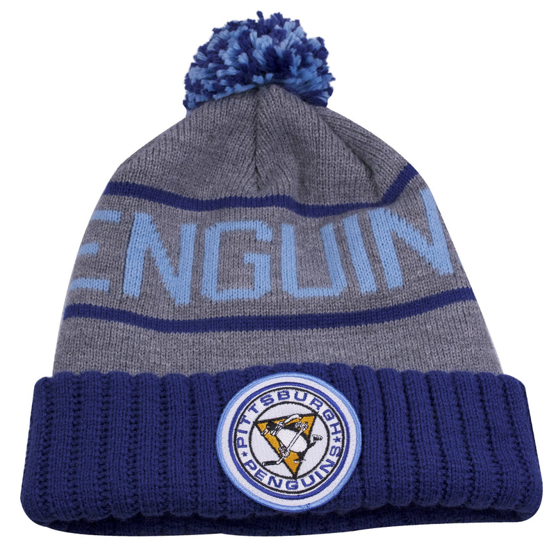 the vintage pittsburgh penguins winter pom beanie has a gray crown and blue raised cuff. On the front of the crown it says penguins in light blue and has a vintage Penguins seal embroidered in white, black, yellow and blue