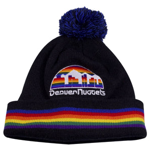 on the front of the denver nuggets vintage black pom beanie is the denver nuggets throwback beanie is embroidered on the crown. The raised cuff features rainbow stripes horizontal on the Denver Nuggets