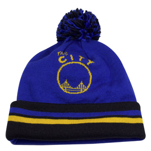 "on the front of the golden state warriors two sided double design winter beanie, the crown is blue, and the raised cuff is black with blue and yellow horizontal lines. The Golden Stat Warriors ""The City"" logo appears in yellow. The pom is black"