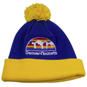 on the front of the denver nuggets vintage blue pom beanie is the denver nuggets logo embroidered in rainbow and white thread. The crown of the winter beanie is blue, the raised cuff is yellow, the pom is also yellow