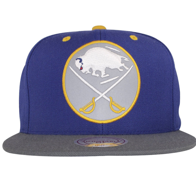 on the front of the reflective buffalo sabres mitchell and ness snapback hat is a reflective sabres logo embroidered in yellow, and white