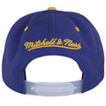 on the back of the reflective buffalo sabres snapback hat is a yellow mitchell and ness logo embroidered above a see through adjustable snap