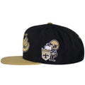 on the left side of the new orleans saints throwback snapback hat is a new orleans vintage logo embroidered in tan, white, and black