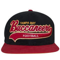 on the front of the retro Tampa Bay Buccaneers snapback hat is the word Buccaneers in a script font embroidered in red, white, and yellow