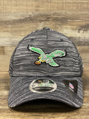 on the front of the Philadelphia Eagles Retro Logo Flyknit Look Space Dye Trucker Dad Hat is a kelly green vintage Eagles logo