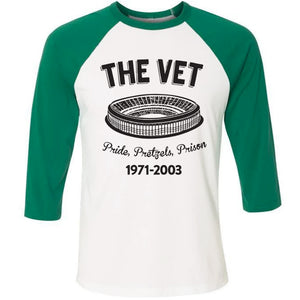 On the front of the veteran's stadium pride pretzels prison 3/4 sleeve baseball tee are the words the vet, an image of veteran's stadium, the words pride, pretzels, prison and the years 1971-2003 printed in black