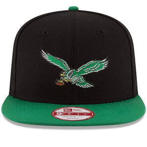 on the front of the Philadelphia Eagles vintage bird two tone snapback hat is the retro Eagles bird logo embroidered in kelly green, white, black, brown and yellow