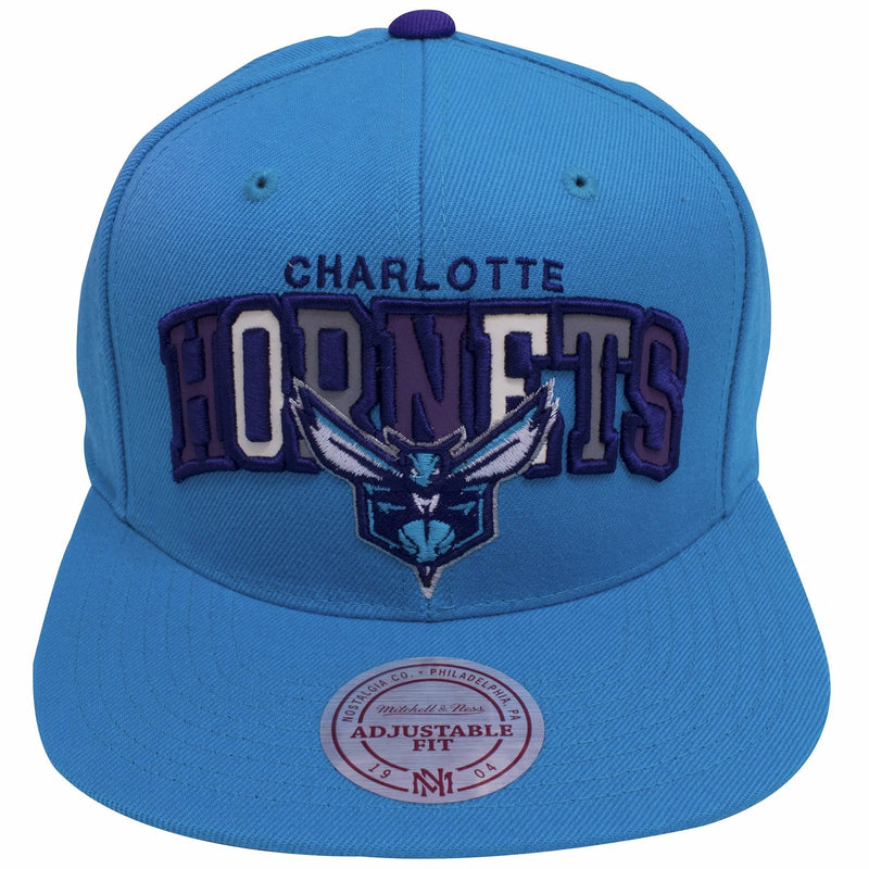 on the front of the charlotte hornets reflective lettering snapback hat are the words charlotte hornets embroidered in purple, the word hornets has reflective lettering above the charlotte hornets logo which is embroidered in teal