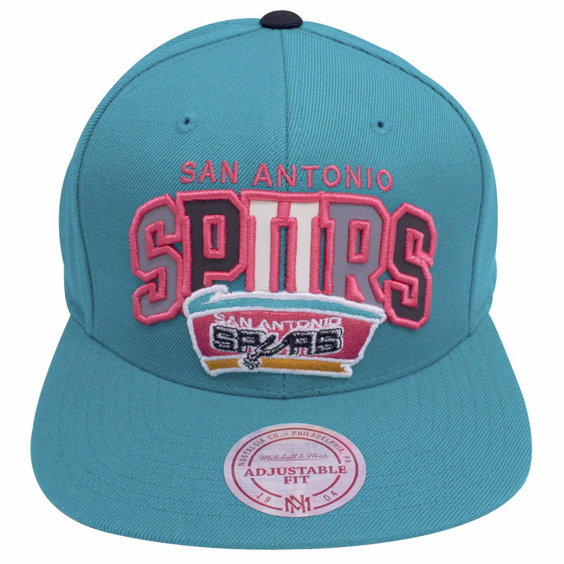 the teal san antonio spurs reflective lettering vintage logo snapback hat features pink lettering that says san antonio spurs, reflective material, and the retro spurs logo embroidered in teal, pink, orange, black, and gray
