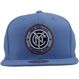 on the front of the new york city football club is a light blue snapback hat embroidered with the new york city football logo in light blue, white, navy blue, and orange