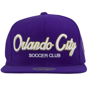 on the front of the orlando city soccer club snapback hat is the word orlando city in white and yellow script above the word soccer club embroidered in white lettering