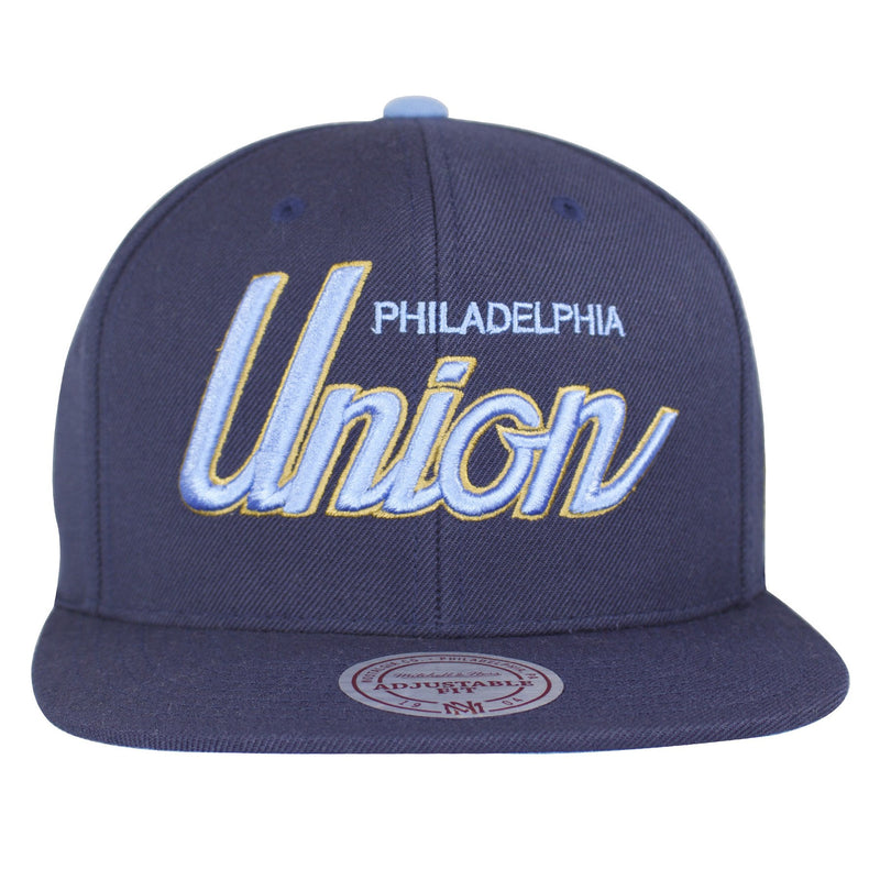 Large Philadelphia Union script writing is heavily embroidered on the front of a structured navy blue snapback hat.