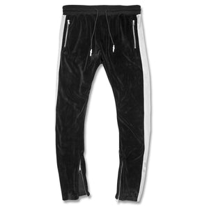 the black and gray velour track suit is black with gray stripes running down the pantleg