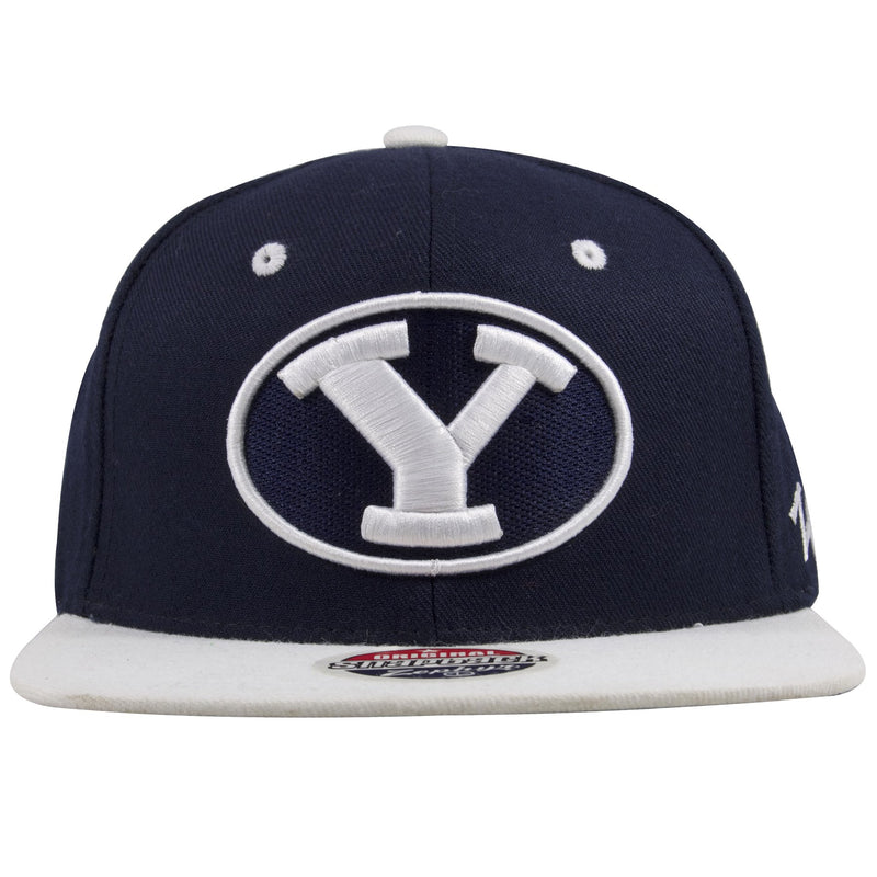 on the front of the byu cougars navy blue on white snapback hat is a byu logo embroidered in white and navy blue