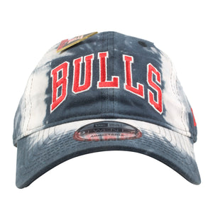 on the front of the bulls tie dye dad hat is the bulls lettering embroidered in red and white