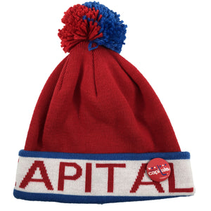 on the front of the washington capitals mitchell and ness winter knit beanie is the word capitals in red