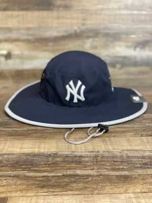 On the front of the New York Yankees Navy Blue Panama Bucket Hat | Wide Brim Stretch Yankees Bucket Hat is a white New York Yankees logo on navy dry-fit material, the hat has a grey stripe around the brim and a drawstring