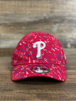 On the front of the Philadelphia Phillies Kids Red Scribble Pattern 9Forty Dad Hat is a white P logo and a tag that says it is toddler size
