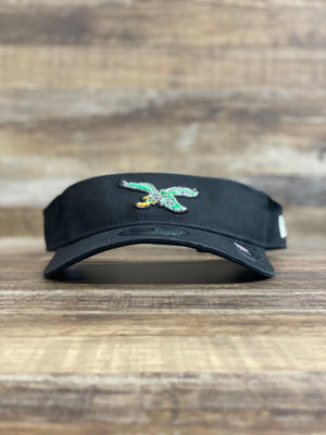 on the front of the Philadelphia Eagles Dugout Redux Retro Black Team Visor is a vintage eagle kelly green logo
