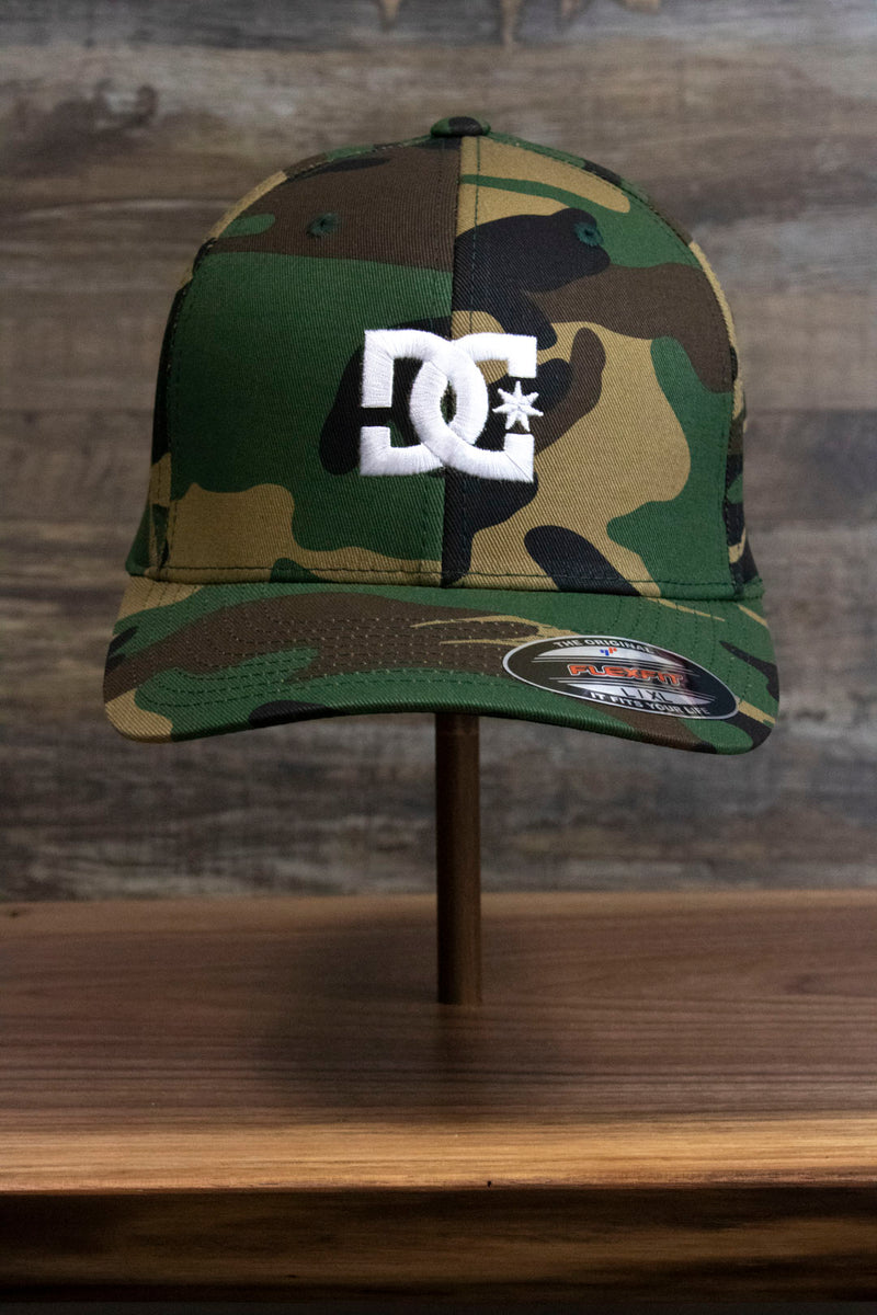 the front of the Camouflage Print Skater Hat | DC Shoes Black Bottom Camo Flexfit Cap has a large white DC Shoes logo on the front