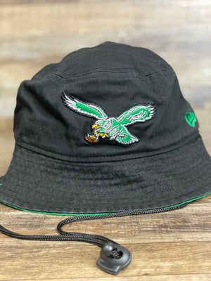 on the front of the Philadelphia Eagles Black Retro Team Adventure Bucket Hat is a kelly green vintage retro Eagles eagle logo
