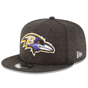The front of the Baltimore Ravens 2018 On Field black snapback hat has the Baltimore Ravens logo embroidered in white, purple, black, red, and yellow