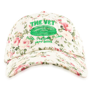 Embroidered on the front of the veterans stadium cream floral dad hat is the vet logo embroidered in kelly green