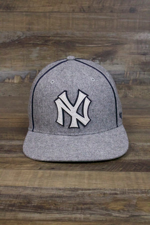 on the front of the New York Yankees Retro Vintage Snapback Hat | Gray Cooperstown Collection Satin Bottom Flat Brim Cap is a felt Cooperstown Yankees logo